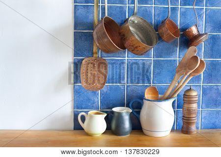 Retro design kitchen interior with accessories. Hanging copper kitchenware set. day light