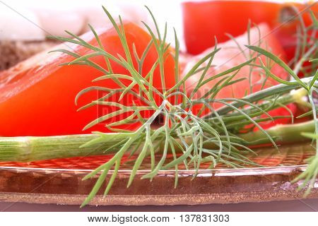 Green sprig of dill on a background a lobule red tomato