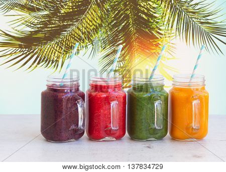 Smoothy drinks in glass jars on white table under plam tree