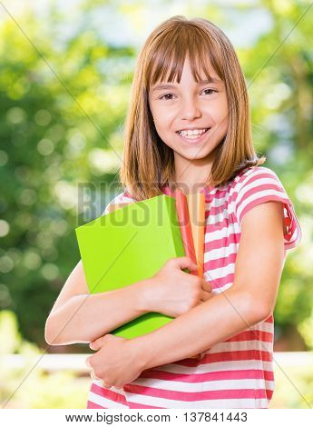 Outdoor portrait of happy girl 10-11 year old with books. Back to school concept.