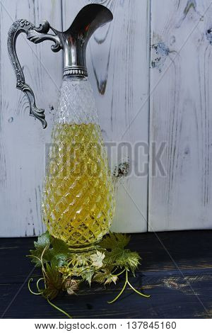 Antique wine pitcher with white wine and grape leaves made from silver and chrystal glass on wooden background
