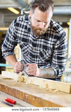 Close-up of a working craftsman with plane in a workshop for woodwork. Handworker with tattoo and beard. Motion blur on planer.