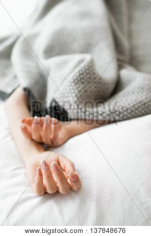 Sleeping introvert hidden from all the people under the blanket. Completely covered with gray blanket woman in bed, with her hands out of blanket. Focus on beautiful female hands with french manicure