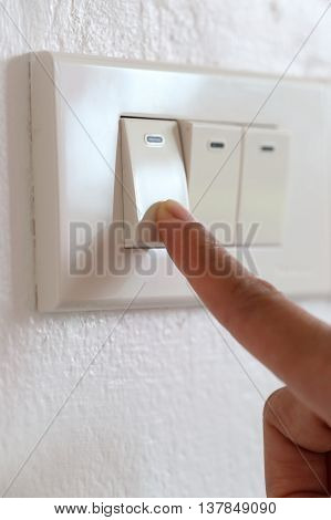 fingers off light switch in the house concept for energy saving reduce global warming.