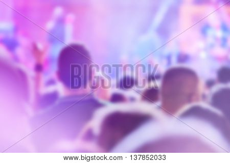 Popular rock music concert crowd out of focus blur unrecognizable group of people listening to live performance on festival stage.