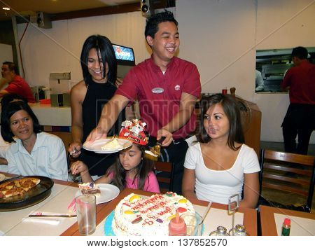 CEBU CITY, CEBU / PHILIPPINES - AUGUST 12, 2011: A waiter at Pizza Hut serves slices of birthday cake at a birthday party in the restaurant in the SM City Cebu shopping mall.