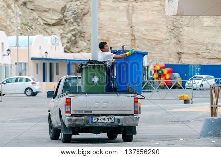 Santorini, Greece - May 2, 2016: Man scavenger unloads garbage cans on the quay at the port Athinios. Santorini Island.