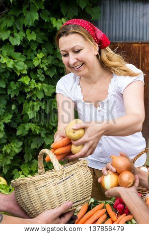A market woman puts the goods sold in a basket