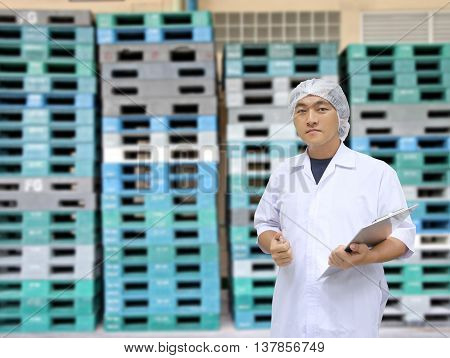 A man in white great coat uniform and Plastic Pallets of background for Concept design Quality Inspection Business.