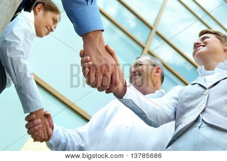 Unter Sicht der Zeilen der glückliche Partner Handshake im Freien auf Grund des Neubaus