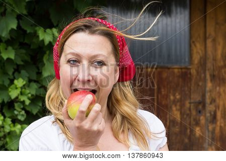A market woman biting with relish into a fresh apple