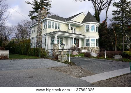 HARBOR SPRINGS, MICHIGAN / UNITED STATES - DECEMBER 25, 2015: A yellow and white home, with a turret and beautiful stonework, on East Bluff Drive in Harbor Springs, with a view of Little Traverse Bay.
