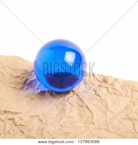 Fragment of a crumbled sheet of paper with the glass ball over it, isolated over the white surface as a copyspace backdrop composition