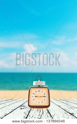 Summer Time, Vintage clock put on wooden with Blurred image of peaceful sea background.