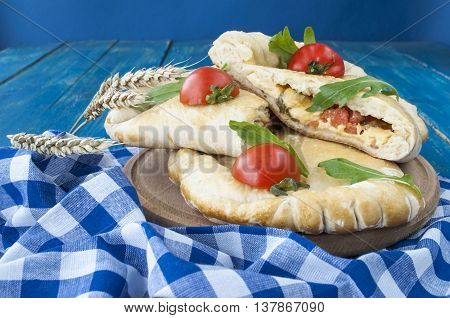 Calzone pizza stuffed with cheese and prosciutto, summer lettuce salad