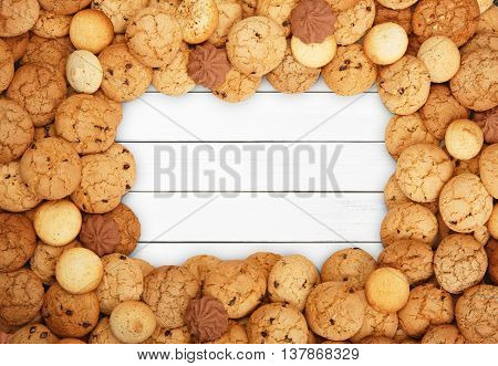 Cookies and sweet biscuits frame at white wood background with copy space. Oatmeal, chocolated drops and other sweets border. Fattening dessert for tea on wooden table top view