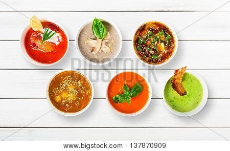 Variety of restaurant hot dishes, healthy food. Japanese miso soup, asian fish soup, russian borscht, english pea soup with bacon, mushroom soup, spanish gazpacho at white wood, top view