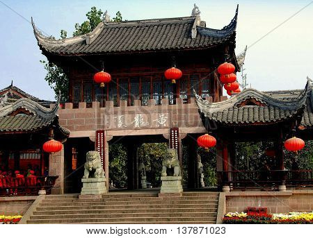 Huang Long Xi China - November 7 2007: Gate of the Scenic Spot with flying eave roofs and decorative red Chinese lanterns flanked by two stone lions