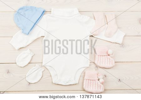 Baby girl and baby boy bodysuit socks gloves and hat on light wooden table. Top view Mock up