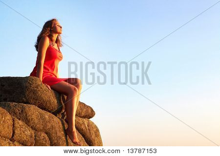 Photo of serene female seated on rock and relaxing