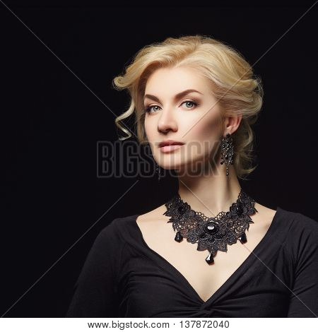 Beautiful blond young woman with natural makup and stylish hairdo. Beauty shot over dark grey background. Copy space.