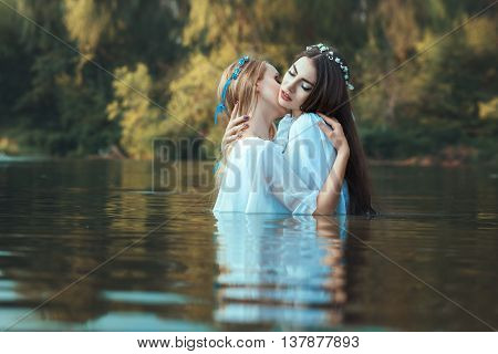 Two women lesbians caress each other while standing in water.