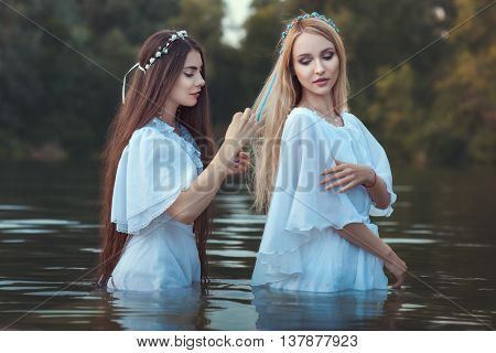 Woman takes care of the hair of her girlfriend they in nature or standing in water.