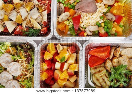 Healthy food background. Take away of natural organic food in foil boxes. Fitness nutrition, meat, vegetable and fruit salads. Top view, flat lay.