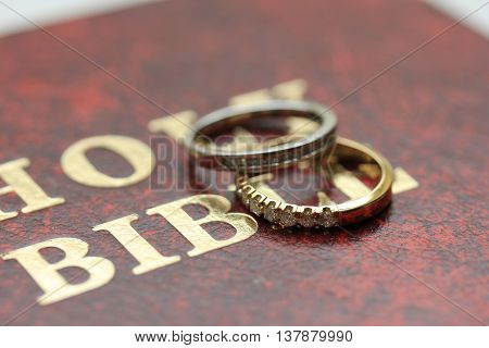 Two diamond wedding bands for a double bride wedding on the cover of the bible