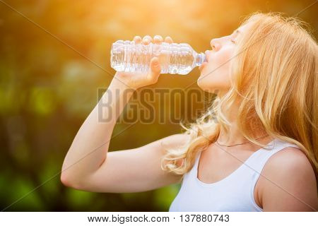 Woman drinking water from bottle on hot sunny day in green park. Image with lens flare effect