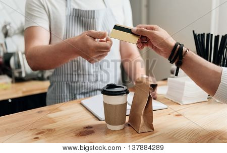 My payment. Cropped image of man paying giving his credit card for waiter to pay at the cafe