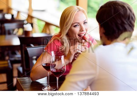 Young man is feeding his girlfriend with strawberry in cafe. Woman is eating and smiling. They are sitting at table and drinking wine