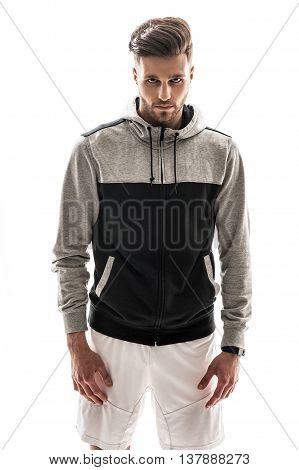 Confident young sportsman is looking at camera with passion. He is standing in sportswear. Isolated