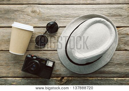 Pretty Hat With Sunglasses, Camera And Drinking Cup On Wooden Table