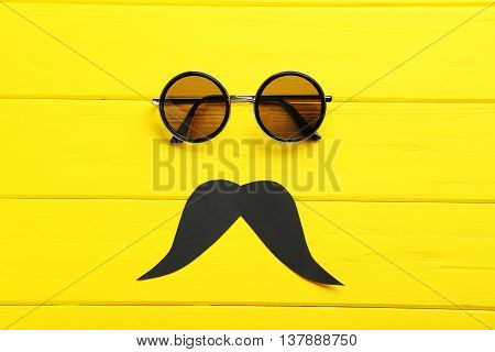 Black Sunglasses And Mustache On A Yellow Wooden Table