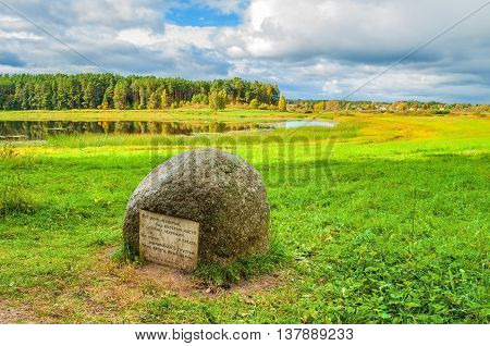 PUSHKINSKIYE GORY RUSSIA - SEPTEMBER 28 2013. Autumn landscape - stone with poems of Pushkin near the Soroti river in museum estate Mikhailovskoe