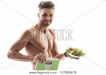 Eat vegetables and lose weight. Cheerful young man is showing scales and plate of salad. He is looking at camera and smiling. Isolated