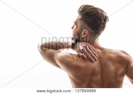 Young man suffers from ache. He is touching neck with despair. Athlete is standing and showing back. Isolated and copy space in left side