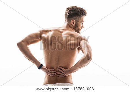 Young sportsman has terrible backache. He is massaging back. Man is standing and looking aside with despair. Isolated and copy space in right side