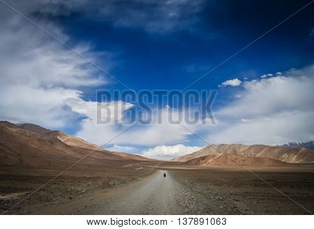 Solo female cyclist cycle touring through the stunning remote landscape of Western Tibet