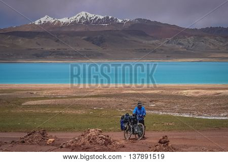 Woman pushing her bicycle uphill on a difficult mountain road on a tibetan plateau, Tibet
