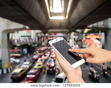 Hand using smart phone on blur background of Traffic jam.