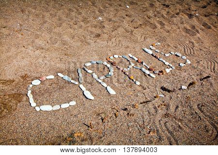 Sign Cyprus made from stones on the beach sand