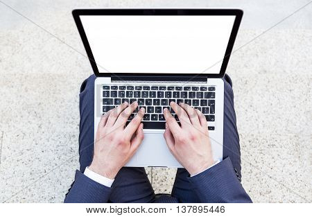 Top view of businessman using laptop with blank screen on concrete background. Mock up
