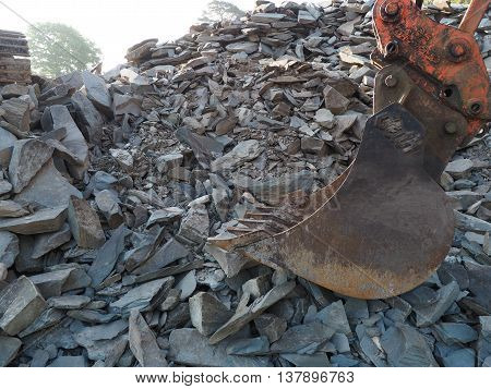 Digger Machine by Grey Slate Rock Pile