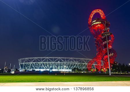 London England - May 27 2016: Night view of the illuminated Olympic stadium and ArcelorMittal Orbit observation tower in the Olympic Park of London England.