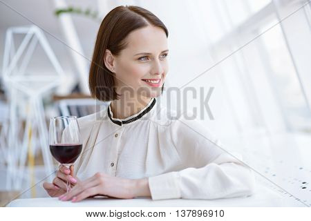 Happy young woman is drinking red wine in restaurant. She is sitting at table and looking through window dreamingly. Lady is smiling