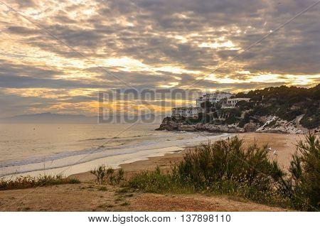 Amber sunset beautiful cloudscape resort on rock few men on the beach. Salou Spain. Summer vacations.concept. Horizontal.