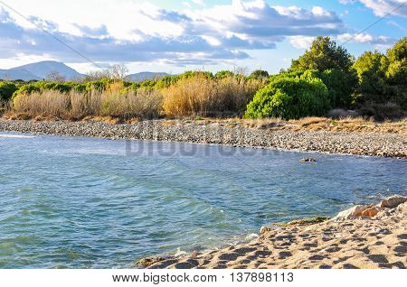 Wild pebble beach with thicket and silhouette of mountains. Catalonia Spain. Horizontal.