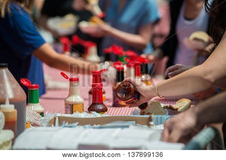 People servering souce and eating food during street food festival